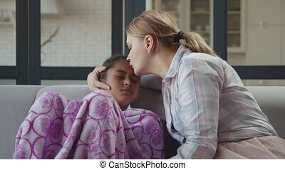 Affectionate mom consoling her ill kid at home