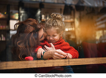 Affectionate mother embracing girl in cafeteria