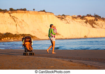 Affectionate mother holding and kissing her baby on beach