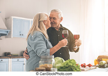 Affectionate old man and woman cooking romantic dinner