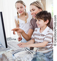 Affectionate parent teaching her children how to use a computer