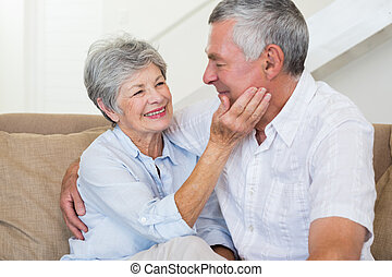 Affectionate retired couple sitting on the sofa at home in...