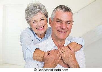 Affectionate retired couple smiling at camera at home in...