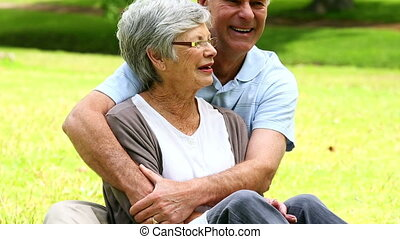 Affectionate senior couple relaxing in the park