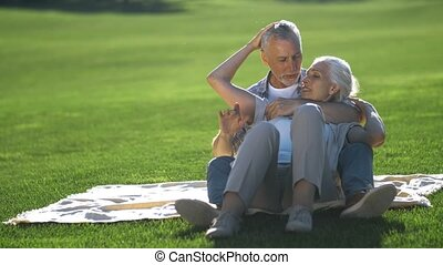 Affectionate senior couple relaxing on green lawn -...