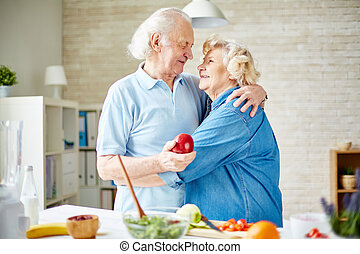 Affectionate seniors embracing in the kitchen