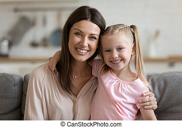 Affectionate single mom and child daughter embracing looking at camera