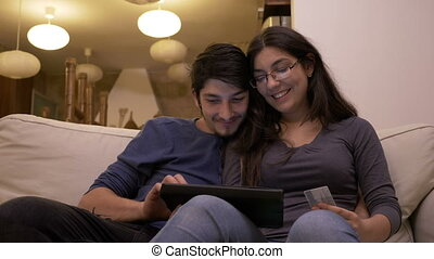 Affectionate young beautiful couple shopping online together using tablet pc at home