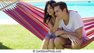 Affectionate young couple sitting on a hammock -...