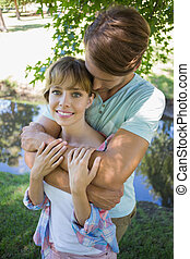 Affectionate young couple standing together in the park girl smiling at camera on a sunny day