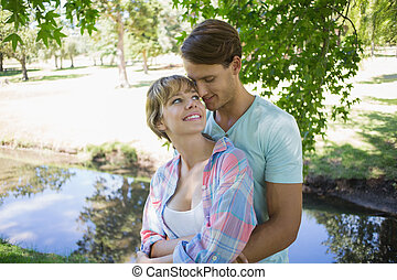 Affectionate young couple standing together in the park