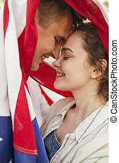 Affectionate Young Couple Under American Flag