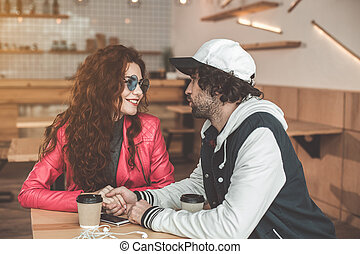 Affectionate young man and woman enjoying date in cafe