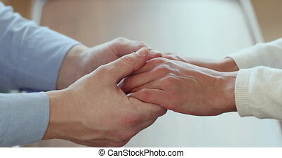 Affectionate young man holding hands of wife, showing ...