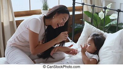 Affectionate young vietnamese ethnic woman playing with kid...