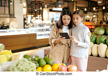 Affectionate young woman and her daughter reading shopping list in notepad