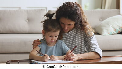 Affectionate young woman babysitter cuddling small cute kid, drawing together.
