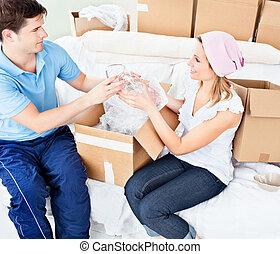 affectueux, jeune couple, désemballant cases, à, lunettes