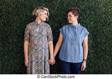 affettuoso, giovane, coppia lesbia, tenere mani, vicino, uno, frondoso, parete