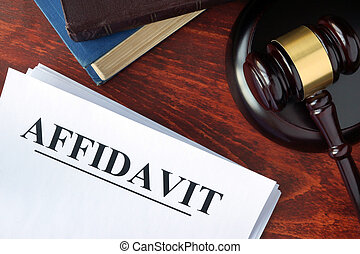Affidavit form, documents and gavel on a table.