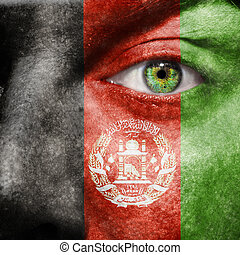 Afghan flag painted on a man's face with a green eye to show...