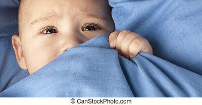 afraid baby under a blue blanket closeup