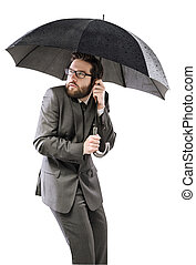 Afraid businessman hiding himself under the umbrella
