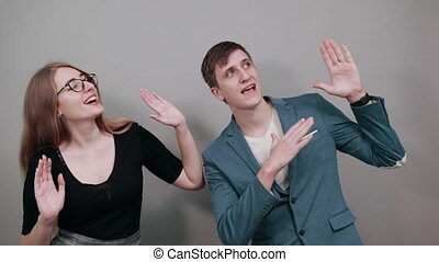 Afraid holding palms to camera as stay there sign, in panic, facial pain, struggles with outstretched hands up, scared domestic abuse, mouth wide open. Young attractive couple two people
