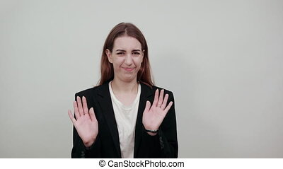 Afraid holding palms to camera as stay there sign, in panic, facial pain, struggles with outstretched hands up, scared domestic abuse, mouth wide open. Young attractive woman with brown hair