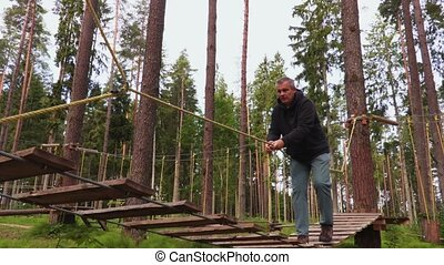 Afraid man walking on rope bridge in park