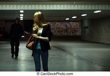 Afraid woman in the subway at night