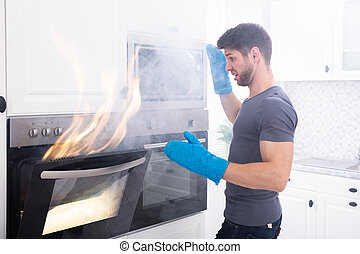 Man Looking At Fire Coming Out From Oven