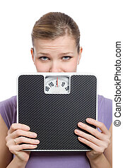 afraid young woman looking behind a weight scale over white background