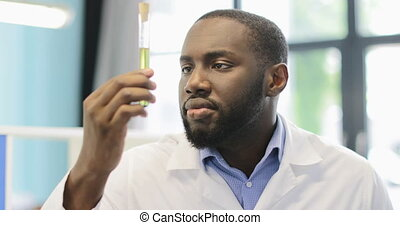 Afriacn American Scientist Analyzing Liquid In Test Tube Explain Result Of Experiment To Group Of Colleagues In Modern Laboratory