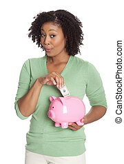 African America young woman inserting currency into piggy bank