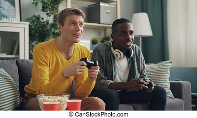 African American and Caucasian guys are playing video game then doing high-five and shaking hands. Modern technology, entertainment and apartment concept.