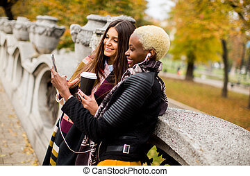 frican american and caucasian woman posing outside