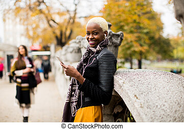 African american and caucasian woman posing outside with mobile phone and a cup of coffee to go in autumn