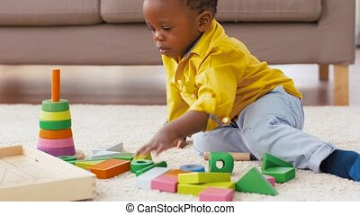 african american baby boy playing with toy blocks -...