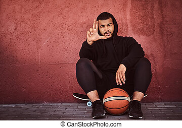 African-American bearded guy dressed in a black hoodie and...