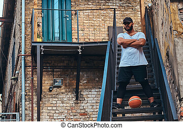 African-American bearded streetball player in cap dressed in...