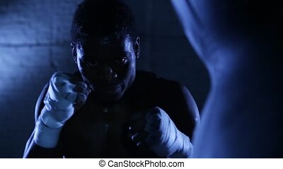 African american boxer athlete shadow boxing in gym