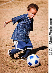 African American boy playing soccer