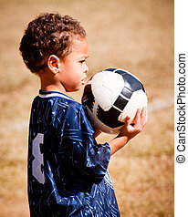African American boy playing soccer - Young African American...