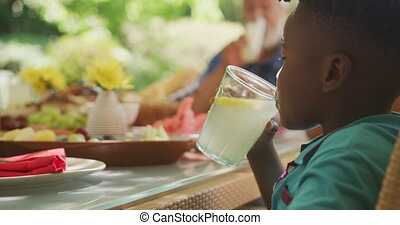 African American boy spending time in garden, sitting at a dinner table with his family, drinking lemonade, in slow motion.