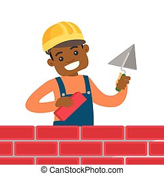 African-american bricklayer building a brick wall.