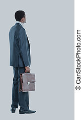 African American business man from the back looking at something isolated white background.