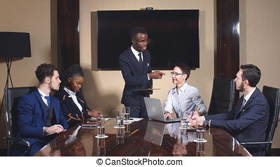 African American Business Man Giving a Presentation to Associates.