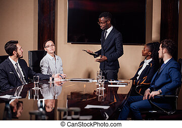 African American business man giving presentation to...