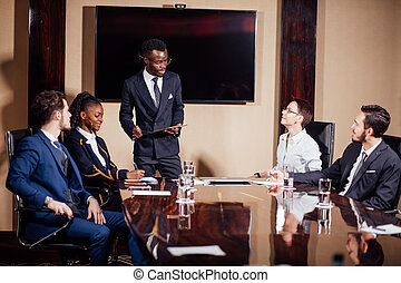 African American business man giving presentation to associates